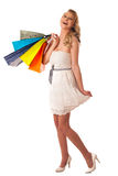 Beautiful young blonde caucasian woman holding vibrant shopping Royalty Free Stock Photos