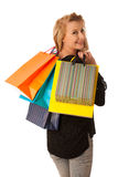 Beautiful young blonde caucasian woman holding vibrant shopping Stock Photos
