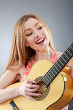 A beautiful young blonde with a classical guitar Royalty Free Stock Photography