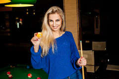 Beautiful young blonde with cue ball in hand smiling Stock Photography