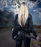 Beautiful young blonde dressed in black leather with electric gu Royalty Free Stock Photography