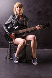 Beautiful young blonde dressed in black leather jacket with electric guitar on a black background Stock Photos