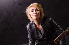 Beautiful young blonde dressed in black leather jacket with electric guitar on a black background Royalty Free Stock Photography