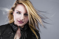 Beautiful young blonde dressed in rocker with hair in the wind Royalty Free Stock Photos