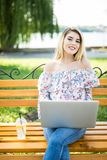 Beautiful young blonde female student using portable laptop computer while sitting on the bench. Young beautiful girl using a pers. Beautiful young blonde female Stock Photography
