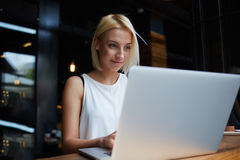 Beautiful young blonde female student using portable laptop computer while work at the coursework, Stock Photo