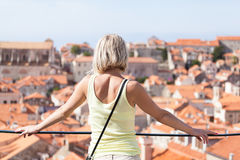 Beautiful young blonde girl on a background of blurred panoramic cityscape. Dubrovnik Royalty Free Stock Images