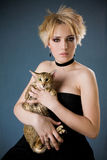 Beautiful young blonde girl in black dress holding. Cat over dark background stock photos