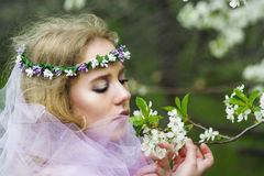 Beautiful young blonde girl in blooming trees Royalty Free Stock Photography