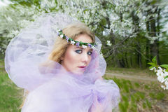 Beautiful young blonde girl in blooming trees Royalty Free Stock Photos