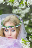 Beautiful young blonde girl in blooming trees Royalty Free Stock Photo