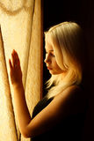 Beautiful young blonde girl. Dramatic portrait of a woman in the dark. Dreamy female look in twilight. Female silhouette stock photo