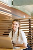 The girl behind the laptop is sitting at a caf Stock Photos
