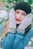 Beautiful young blonde girl in hat and mittens covers his face outside in the cold, Effect retro photo, grain Royalty Free Stock Photography
