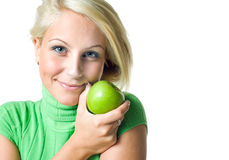 Beautiful young blonde girl hodinga green apple. Royalty Free Stock Images