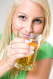 Beautiful young blonde girl holding apple juice. Beautiful young blonde girl holding a glass of apple juice, focus on the face Royalty Free Stock Photography