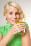 Beautiful young blonde girl holding apple juice. Beautiful young blonde girl holding a glass of apple juice, focus on the face Royalty Free Stock Photo
