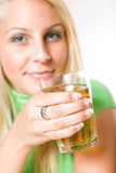 Beautiful young blonde girl holding apple juice. Beautiful young blonde girl holding a glass of apple juice, focus on the glass Stock Photo