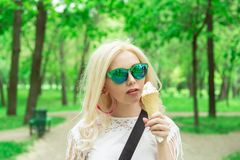 Beautiful, young blonde girl with ice cream in her hands, licks the ice cream on the background of a green park. Italian ice cream. In the hands of the girl royalty free stock photos