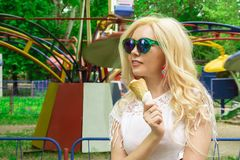 Beautiful, young blonde girl with ice cream in her hands, licks the ice cream on the background of a green park. Italian ice cream. In the hands of the girl royalty free stock photography