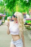 Beautiful, young blonde girl with ice cream in her hands, licks the ice cream on the background of a green park. Italian ice cream. In the hands of the girl stock photography