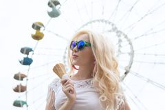 Beautiful, young blonde girl with ice cream in her hands, licks the ice cream on the background of a green park. Italian ice cream. In the hands of the girl royalty free stock images