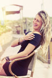 Beautiful young blonde girl laughing outdoor. A beautiful young girl is laughing. She is happy. Sitting outdoors with warm, intense summer sunlight Stock Photo