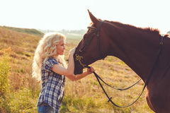 Beautiful young blonde girl is looking in her horse eyes. royalty free stock images