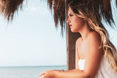 Beautiful young blonde girl looking out over the sea. stock photography