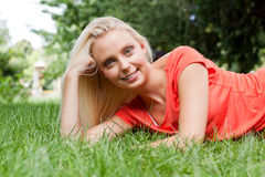 Beautiful young blonde girl lying in grass summertime Stock Photography