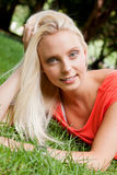 Beautiful young blonde girl lying in grass summertime Stock Images