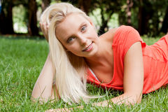 Beautiful young blonde girl lying in grass summertime Stock Photo