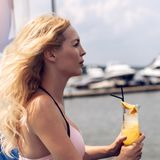 Beautiful young blonde girl in pink bikini drinks cocktail with juice at the resort royalty free stock images