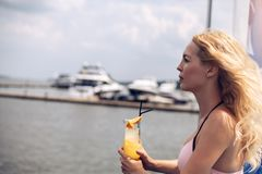 Beautiful young blonde girl in pink bikini drinks cocktail with juice at the resort royalty free stock photography