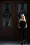 Beautiful young blonde girl posing on the background of Burgundy doors. woman in a black dress. The girl on the background. royalty free stock image