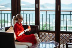 Beautiful young blonde girl in red dress and sunglasses drinking red cocktail from a glass on an open terrace of an royalty free stock image
