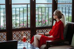 Beautiful young blonde girl in red dress and sunglasses drinking red cocktail from a glass on an open terrace of an stock photography