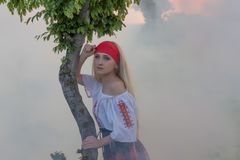 Beautiful young blonde girl with a red scarf, a traditional romanian blouse and a red and black skirt. Covered in smoke, Romania Royalty Free Stock Photo