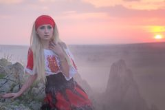 Beautiful young blonde girl with a red scarf, a traditional romanian blouse and a red and black skirt. Covered in smoke at sunset, Romania Royalty Free Stock Photography