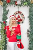 A beautiful young blonde girl in a Santa`s cap stands at the front door decorated with a wreath and branches of spruce royalty free stock images