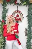 A beautiful young blonde girl in a Santa`s cap stands at the front door decorated with a wreath and branches of spruce royalty free stock photos