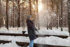 A beautiful young blonde girl in a winter coniferous forest is standing and catching with her hands the snow falling from the royalty free stock photo
