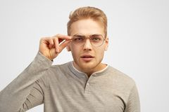 Beautiful young blonde guy holding glasses and squinting trying to read the inscription in front of him. stock photos