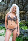 Beautiful young blonde haired woman at beach in bikini smiling Stock Photo