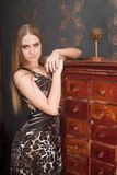Beautiful young blonde haired woman opens drawer Royalty Free Stock Image