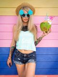 Beautiful young blonde hipster in denim shorts and a straw hat, sunglasses stands amid the brightly colored walls with a. Coconut in hand. Tropical weekend royalty free stock image