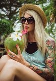 Beautiful young blonde hipster in a straw hat and sunglasses sitting in a tropical garden with coconut in hand. Rain royalty free stock image