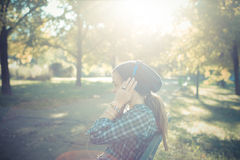 Beautiful young blonde hipster woman listening music royalty free stock photography
