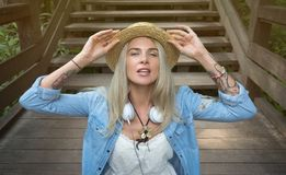 Beautiful young blonde hipster woman in a straw hat sitting on the wooden steps in the Park, looking at the camera. The. Woman is dressed in a denim shirt and Stock Photo
