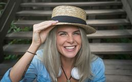 Beautiful young blonde hipster woman in a straw hat sitting on the wooden steps in the Park smiling looking at camera Royalty Free Stock Photography